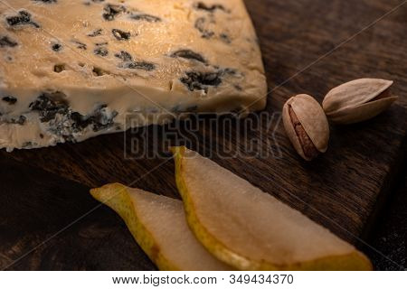 Close Up View Of Cheese Platter With Dorblu, Sliced Pear And Pistachios