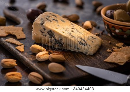 Selective Focus Of Cheese Platter With Dorblu, Olives, Crackers And Pistachios Near Knife