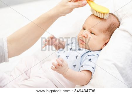 Mother brushing hair of her newborn baby using soft hairbrush to stimulate infant's hair follicles and increase scalp blood flow for healthy hair growth
