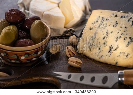 Selective Focus Of Dorblu And Brie Cheese With Olives And Pistachios Near Knife