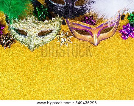 Colorful Mardi Gras Carnival Masks On Golden Glitter Background. Festive Holiday Still Life Flat Lay