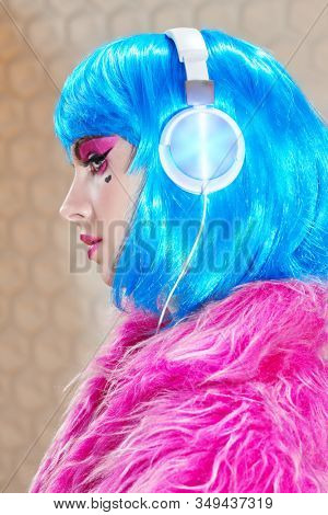 Sideview portrait of an attractive party girl with bright pink makeup and blue wig wearing pink fur coat and headphones. DJ girl.