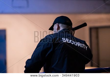 Security Guard Walking Building Perimeter With Flashlight At Night