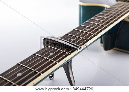 A Capotasto On A Fretboard Of Acoustic Guitar, On A White Background, Close-up.