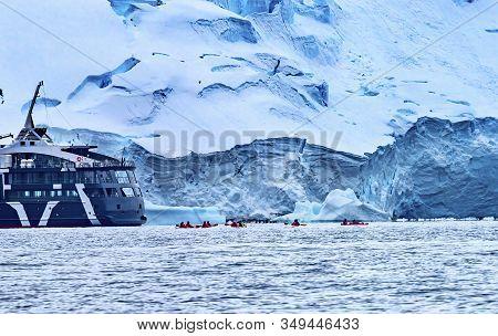 Ship Red Kayaks Tourists Glaciers Snow Mountans Charlotte Bay Antarctic Peninsula Antarctica.  Glaci