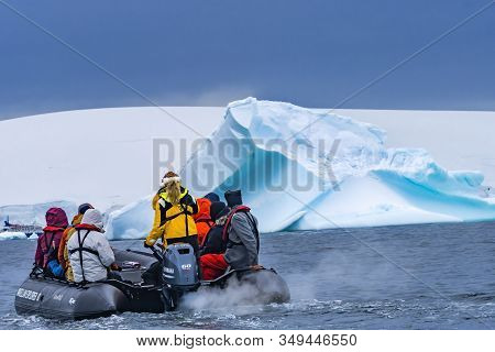 Charlotte Bay, Antarctica - December 26, 2019 Tourists Rubber Boat Blue Iceberg Glaciers Snow Mounta