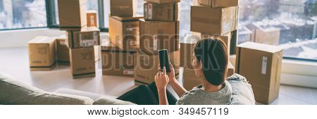 Moving boxes woman using phone panoramic for move to college leaving apartment ready for movers pick-up with packages of cardboard box for new home move in. Banner.