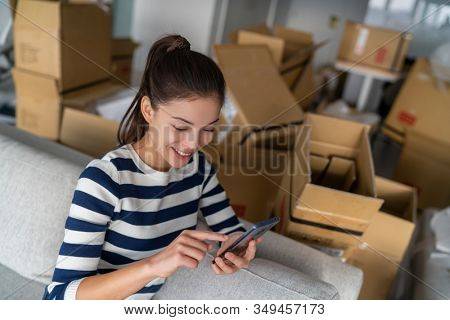 Homeowner Asian woman using cellphone mobile phone for indoor mess with many open packages moving boxes for move in new apartment. Happy girl in condo house.