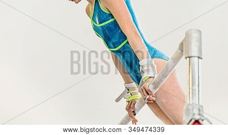 Girl Gymnast Exercise Uneven Bars In Gymnastics On Light Background
