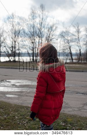 Portrait Of A Cute Little Girl Of 8-9 Years Old, Wearing Bright Red Jacket. Girl 9 Years Old To A Re