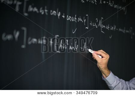 Math teacher by the blackboard during mathclass - detail of the hand with chalk