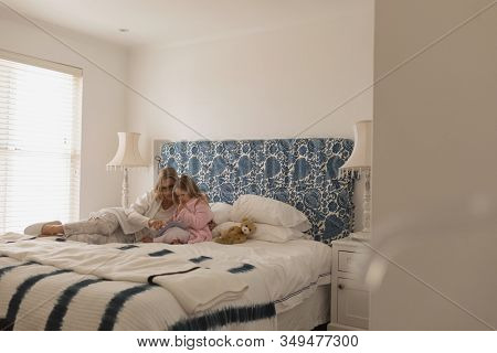 Distant side view of mother with her young daughter reading storybook in bedroom at home