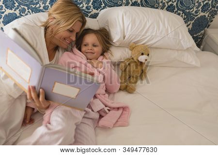 High angle view of happy mother with her young daughter reading storybook in bedroom at home