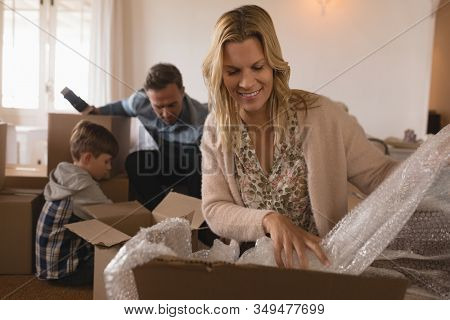Front view of happy family unpacking cardboard boxes in their new home