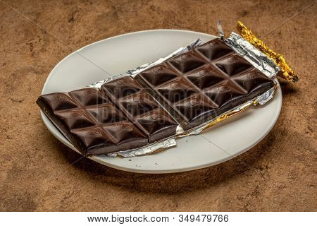 unwrapped and broken chocolate bar on white plate against brown textured paper