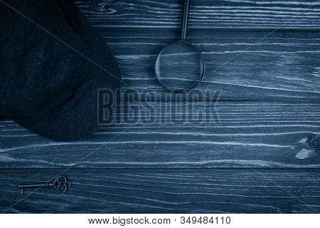 Detective Cap, A Key And A Magnifying Glass On A Worn Wooden Background Toned In The Classic Blue Co