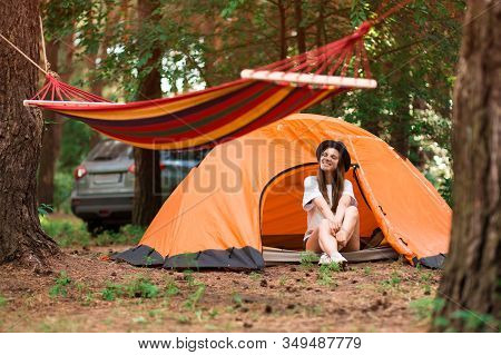 Beautiful Woman Sitting Outside Tent Enjoying Holiday Away From Bustle Of City In Forest.