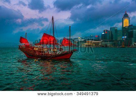 The Chinese Red-sail Junk Boat In Hong Kong Harbor At Night In China.