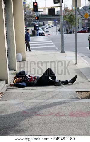 2-5-2020 China Town, Los Angeles CA. A person sleeps or enjoys the cold morning laying on the sidewalk of China Town in Los Angeles CA. Editorial use only.