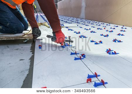 Tiler Using Plastic Clamps And Wedges To Leveling Ceramic Tile On The Floor.