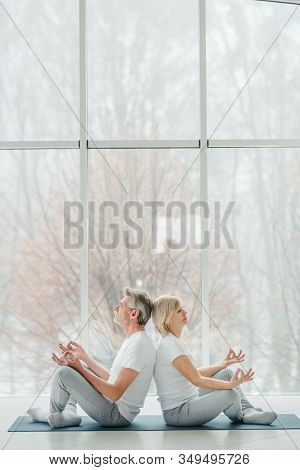 Harmony And Calm. Beautiful Senior Couple Doing Yoga Together In The White Gym With Panoramic Window