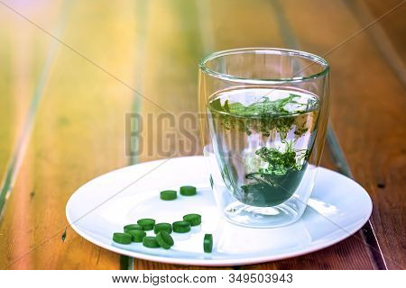Chlorophyll In A Glass Of Water And Green Pills Of Spirulina On A Plate On Wooden Table. Copy Space,