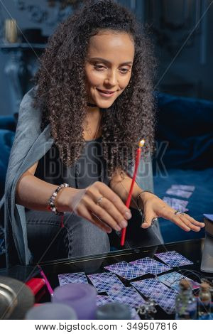 Smiling Soothsayer Using A Burning Wax Taper