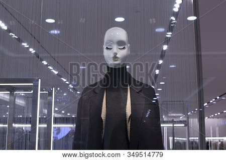 One Bald Female Mannequin With Eyelashes And Eyes Closed On A Shop Window In Strict Dull Black And G