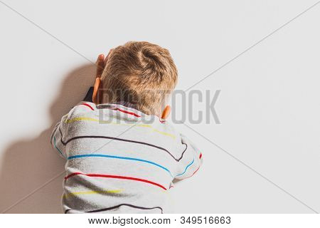 Frustrated Little 2 Years Boy Crying Near The Wall