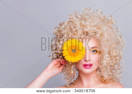 Beautiful Fashionable Blonde Girl With Voluminous Curly Hairstyle, Bare Shoulders And A Sunflower In
