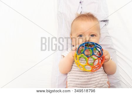 Little Cute Baby Toddler Play With Colorful Plastic Ball Laying On The Back And Hold Toy Near Mouth