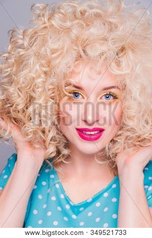 Beautiful Blonde Girl In Retro Style With Voluminous Curly Hairstyle, In A Blue Polka-dot Blouse On