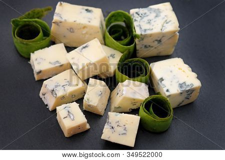 Blue Cheese Cubes On A Black Background. Blue Cheese On A Slate Board. Roquefort Cheese On A Plate.