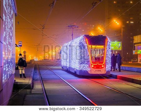 Moscow.russia. December 26, 2019. Trams In The Fog Lit By A Network Of Leds Arrive At A Bus Stop Wit