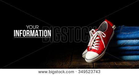 Fashionable Clothes. Pile Of Jeans, Red Sneakers On A Wooden Background, Space For Text