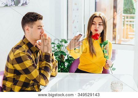 Loving Boy And Girl Sitting In Cafe, Girl Looking Happy, Taking Selfie With Flower, While Boy Doesnt