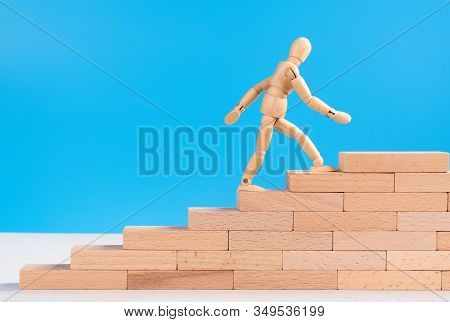 Figure Of Wooden Man Climb Up The Stairs Of Success Or Career.