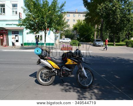 Russia, The City Of Murom. July 09, 2018. Yellow Enduro Motorcycle With Things On A City Street.