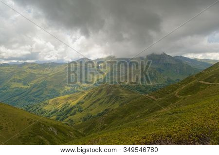 Low Clouds Over A Mountain Valley In The Caucasian Mountains. The Far Mountain Peak Is Covered With