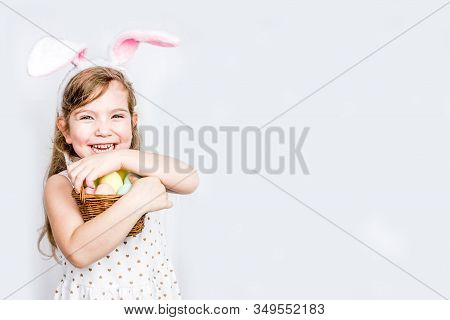 Happy Cute Child Girl In Rabbit Costume With Bunny Ears Holds Basket Painted Eggs In Hands. Easter D