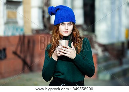 Young Stylish Woman Drinking Tea In A City Street. Hipster European Girl With Latte Paper Glass In S