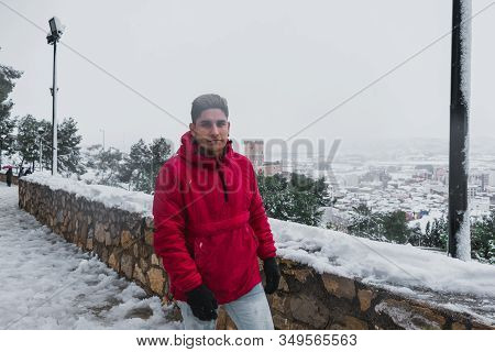 Young Latin Man Walks Through A Snowy Town With A Castle In The Background. Lifestyle And Travel Con