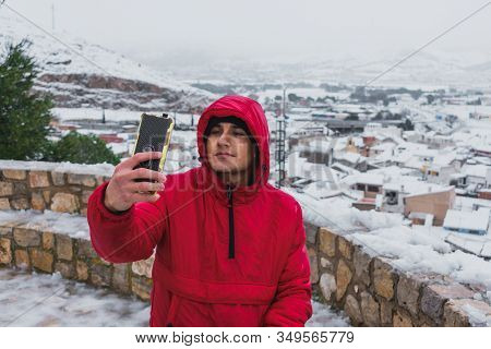 Young Latin Man Is Taking A Self Portrait In A Snowy Town. Lifestyle Concept