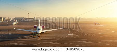 Colorful Scenic Dramatic Morning Sunset At Airport Asphalt Taxiway And Parking With Different Commer