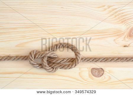 Marine Knot Used In Yachting, Bowline Knot. Nautical Knot On Wooden Background.