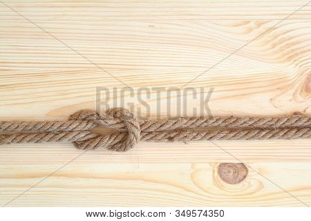 Marine Knot Used In Yachting, Square Knot. Nautical Knot On Wooden Background.