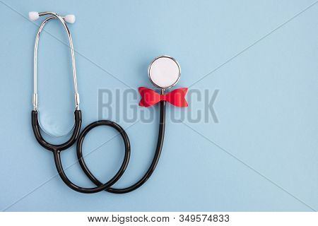 Doctor`s Day And World Health Day Concept. Medical Stethoscope In A Festive Red Bow On Light Blue Ba