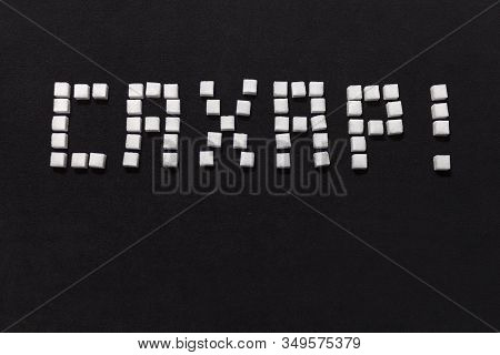The Word Sugar In Stacked Of Sugar Cubes In Russian On A Black Background.