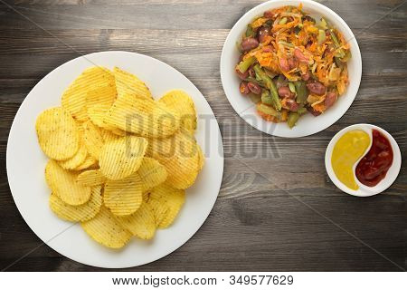 Potato Chips On A White Plate With Vegetarion Salad. Chips On A Black Wooden Background Top View.