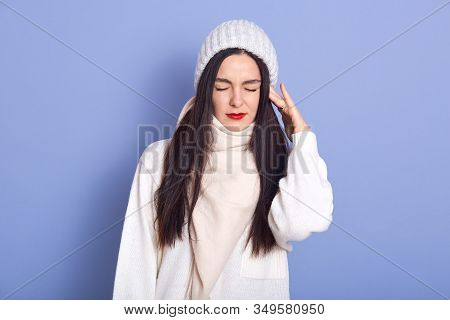 Horizontal Picture Of Young Attractive Woman Standing Isolated Over Blue Background In Studio, Putti
